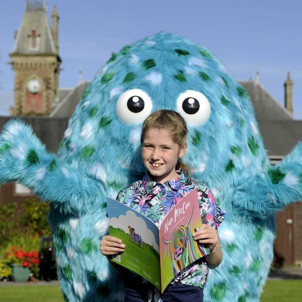 Bigwig, the children's festival mascot in the town square with a young reader.